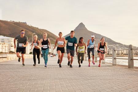 Diverse Gruppe von Jugendlichen, die entlang einer Strandpromenade läuft. Fit junge Läufer im Freien Training am Meer.