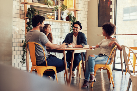 Mladí lidé sedí u stolku v kavárně. Skupina přátel mluví v kavárně.