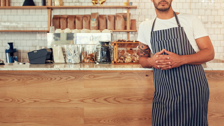 clasped hand: Cropped shot young man standing at a coffee shop counter wearing an apron. He is leaning to the cafe counter with his hands clasped. Stock Photo