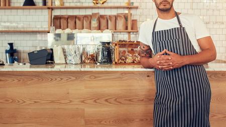 mostradores: joven cultivada foto de pie en un mostrador de tienda de café que lleva un delantal. Él se inclina hacia el mostrador café con las manos cruzadas. Foto de archivo