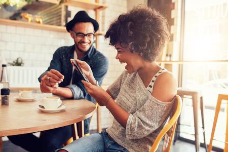 Retrato de mujer joven sonriente en una mesa de café que mira la tablilla digital con un amigo sentado junto.