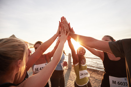 Athletic team met hun handen in elkaar gestapeld vieren succes. Marathonlopers geeft high five.