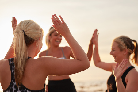 Runners giving high five to each other after a good training session. Group of athletes celebrating success. Stock Photo