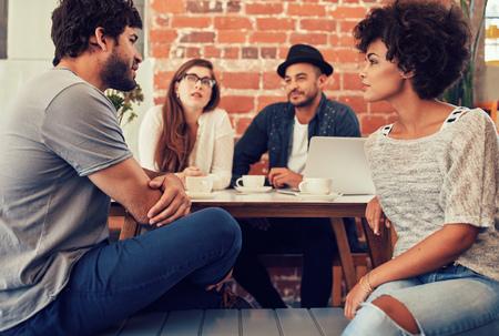 Grupa młodych przyjaciół siedzi i rozmawia w kawiarni. Młodzi mężczyźni i kobiety spotkania w kawiarni i omawianie. Zdjęcie Seryjne