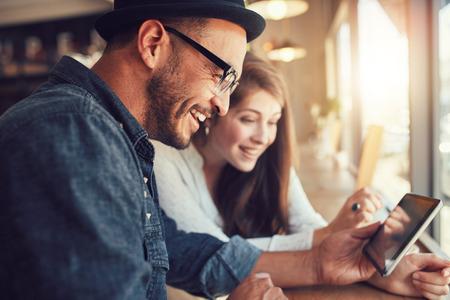 technologia: Zamknij się portret szczęśliwa młoda para przy użyciu cyfrowego tabletu razem w kawiarni. Młody mężczyzna i kobieta, patrząc na ekranie dotykowym komputera i uśmiechnięte.