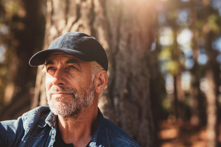 Close up portrait of senior man wearing cap looking away. Mature man with beard sitting in woods on a summer day. Stock Photo