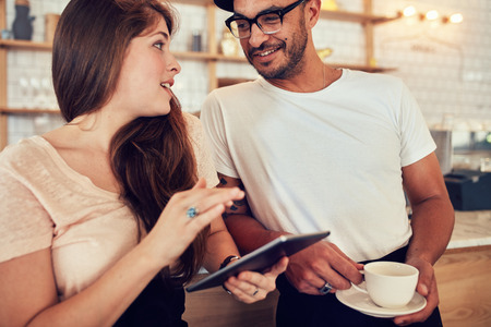 over the counter: Portrait of happy young couple at cafe counter having discussion over a cup of coffee. Woman holding a digital tablet and man with cup of coffee.