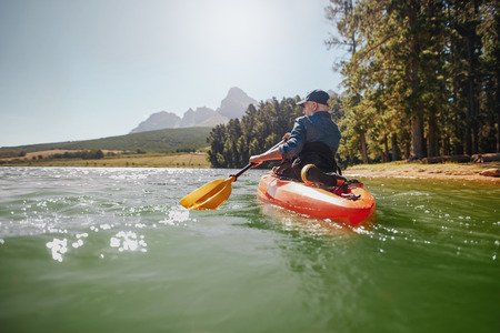 lifestyle outdoors: Rear view of a mature man canoeing in a lake. Senior man paddling kayak on a summer day. Stock Photo