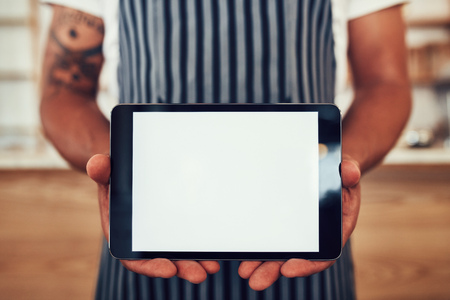 tab: Close up portrait of a man wearing an apron holding a digital tablet with a blank white screen. Waiter holding a touch screen tab with copy space for your text.