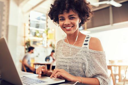 Portret van gelukkige jonge Afrikaanse vrouw met een laptop op cafe. Lachende vrouw zitten in de coffeeshop met een laptop. Stockfoto