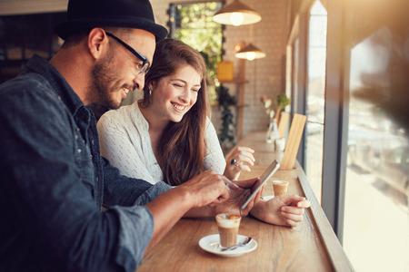 novio: feliz pareja en un café Internet que practica surf en la tablilla digital. hombre y una mujer en un restaurante que mira el ordenador de pantalla táctil. Foto de archivo