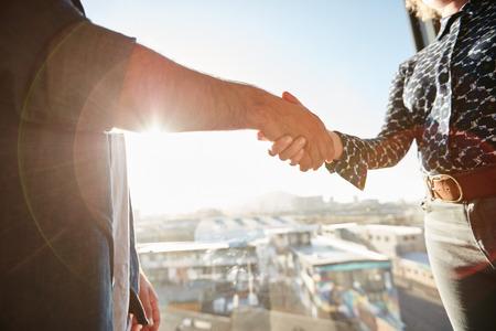 Handdruk van twee medewerkers met zonlicht. Man executive schudde zijn hand met vrouwelijke collega, focus op handen.