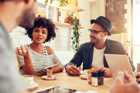 Portret van een jonge vrouw te praten met vrienden in een cafe. Groep jonge mensen bijeen op een coffeeshop.