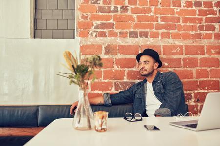 soledad: Retrato de hombre joven con sombrero sentado solo en un café con el ordenador portátil sobre la mesa. El hombre que espera alguien en la cafetería. Foto de archivo