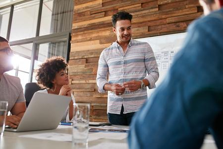 Portrét mladého muže s kolegy se schůzky v konferenční místnosti. Různá skupina mladých návrhářů brainstorming v zasedací místnosti. Reklamní fotografie