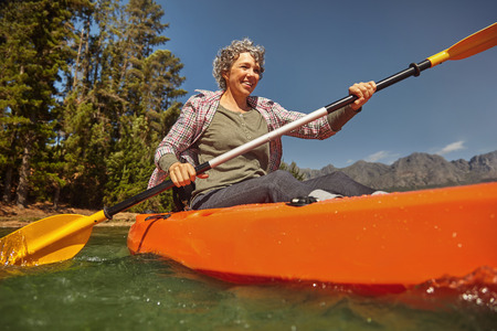 canoeing: Portrait of senior woman paddling in a lake. Happy mature caucasian woman canoeing on summer day. Stock Photo