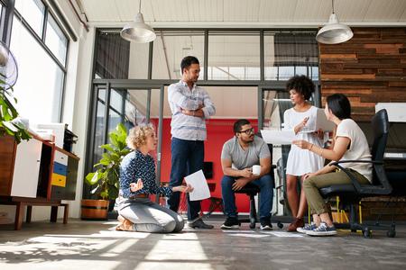 Creatief team met een discussie over nieuw ontwerp project in het kantoor. Projectplan gelegd op de vloer met collega vergadering en bespreken.