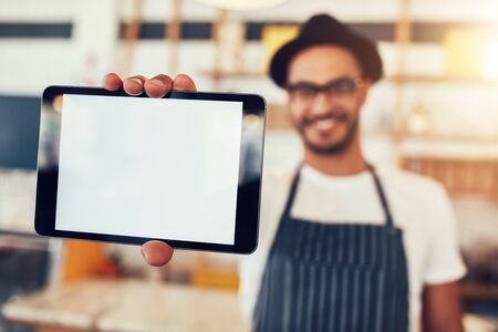 tab: Close up portrait of a man holding up a digital tablet with a blank display. Man working in cafe showing a touch screen computer.