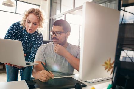 Tiro de dois designers que trabalham em seu escritório usando um laptop, tabuleta digital de vídeo e computador de mesa. Homem sentado à sua mesa com o colega fêmea que mostra algo em seu laptop.