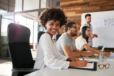 회의실에서 동료와 함께 비즈니스 프레젠테이션에 앉아 행복 한 젊은 흑인 여자의 초상화입니다. 회의실에서 동료와 함께 여성 디자이너. 스톡 콘텐츠