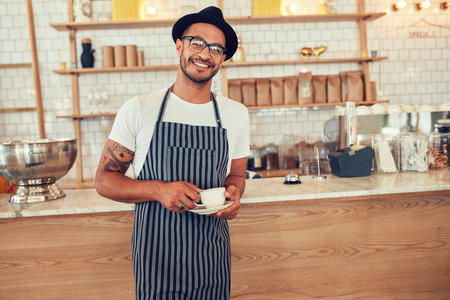 mandil: Retrato de barista joven feliz en el trabajo. hombre de raza caucásica usar delantal y sombrero de pie en frente del mostrador de café con la taza de café y mirando a la cámara sonriendo.
