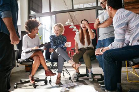 Plan d'un groupe de jeunes professionnels ayant une réunion. Groupe diversifié de jeunes designers en souriant lors d'une réunion au bureau. Banque d'images - 52678088