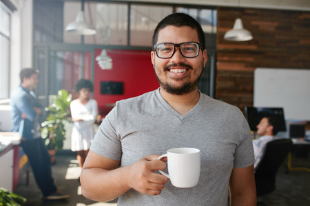 real: Portrait of smiling office worker having a coffee with his colleagues talking in the background.