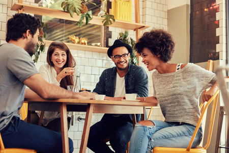 Portrait of cheerful young friends having fun while talking in a cafe. Group of young people meeting in a cafe. Stock Photo