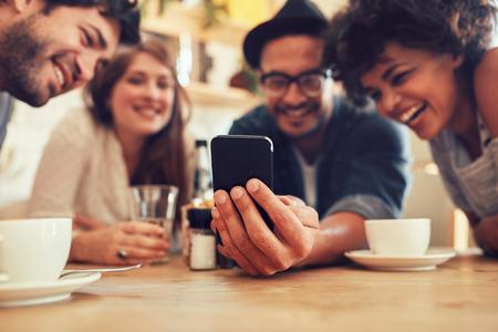 Gruppo di amici che hanno divertimento al caffè e guardando smart phone. L'uomo che mostra qualcosa ai suoi amici seduti, si concentrano sul cellulare.