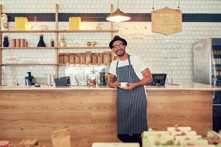 Portret van gelukkige jonge man met een schort en hoed staande in een cafe balie met een kopje koffie. Koffieshop eigenaar op zoek naar een camera en lacht. Stockfoto
