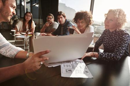 Closeup strzał z zespołem młodych ludzi wykraczających ponad słuchaczowi. Kreatywnych ludzi zebranych w restauracji tabeli. Koncentrują się na ręce i dokumentów.
