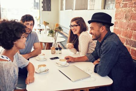 젊은 친구의 그룹은 카페에서 놀고. 젊은 남자와 여자 함께 앉아 커피 숍에서 이야기.