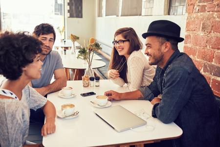 Groep jonge vrienden die op een café hangen. Jonge mannen en vrouwen zitten samen en praten in een koffiewinkel.