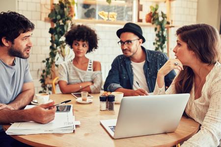 肖像的年輕人圍坐在咖啡館用筆記本電腦的。在一家咖啡店的創意團隊會議以討論新的業務項目。 版權商用圖片