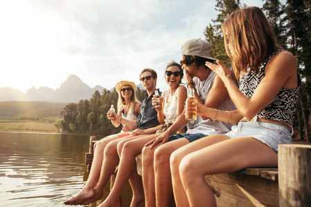 ビール片手に湖の桟橋の上に座って幸せな若い友人の肖像画。若い男性と女性が湖を楽しみます。 写真素材