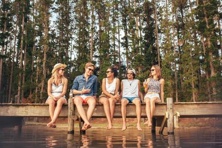 Retrato de jóvenes amigos que se sientan en el embarcadero y hablar. hombres y mujeres jóvenes que disfrutan de un día en el lago. Foto de archivo