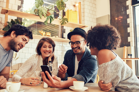 カフェで会うと携帯電話で写真を見て若い友人のグループの肖像画。カフェのテーブルに座っていると、スマート フォンを使用する若い男女
