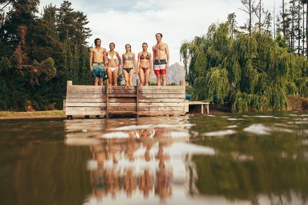 湖の桟橋の端に立っている若い人々 のグループの肖像画。桟橋の行に立っている若い友人。