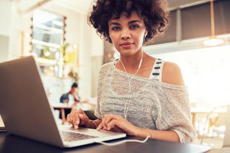 mujeres africanas: Retrato de mujer joven con un ordenador portátil en el café. mujer africana que se sienta en la cafetería con un ordenador portátil.