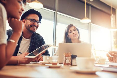 Portret szczęśliwy młody człowiek siedzi i rozmawia z przyjaciółmi w kawiarni. Młodzi ludzie w kawiarni z cyfrowym tablecie i laptopie. Zdjęcie Seryjne