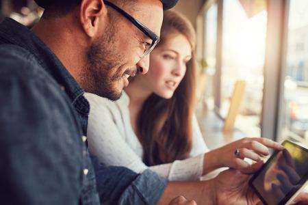 Homem novo feliz com sua namorada em uma loja de café surf internet no tablet digital. Jovem casal em um restaurante que olha o computador da tela de toque.