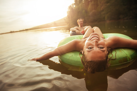 Portrait of happy young woman floating in an innertube with her boyfriend in background at the lake. Young couple in lake on inflatable rings.