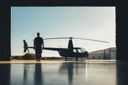 pilotos aviadores: Silueta de helicóptero con un piloto en el hangar de aviones. Piloto caminar lejos de helicóptero estacionado fuera del hangar.