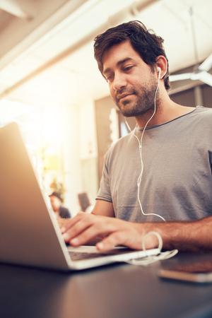 internet cafe: Retrato de hombre joven que busca ocupado trabajando en la computadora port�til en un caf�. hombre cauc�sico que se sienta en la tienda de caf� usando la computadora port�til.