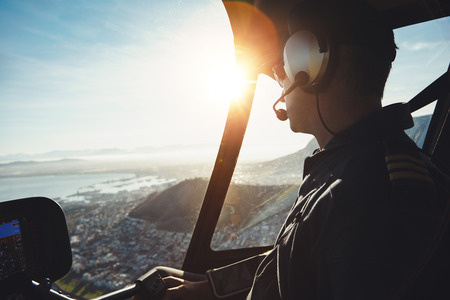 emergency: Close up of a helicopter pilot flying aircraft over a city on a sunny day