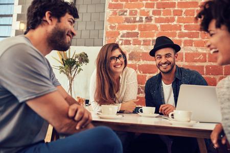 Skupina mladých přátel visí ven v kavárně. Mladí muži a ženy na setkání v kavárně baví.
