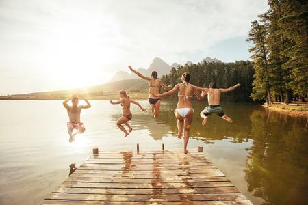 Ritratto di giovani amici che saltano in acqua da un molo. Giovani che hanno divertimento al lago in una giornata estiva.