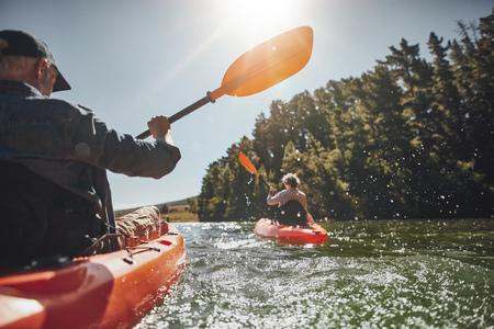 여름 날 백그라운드에서 여자와 호수에 수석 남자 카누의 야외 샷. 남자와 화창한 날에 호수에서 두 개의 서로 다른 카약에서 여자. 스톡 콘텐츠