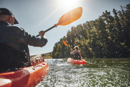 couple nature: Outdoor shot of senior man canoeing in the lake with woman in background on a summer day. Man and woman in two different kayaks in the lake on a sunny day.