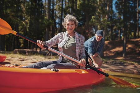 Портрет счастливый старший женщина в байдарке холдинг лопатками. Женщина с мужчиной на каноэ в фоновом режиме на озере.